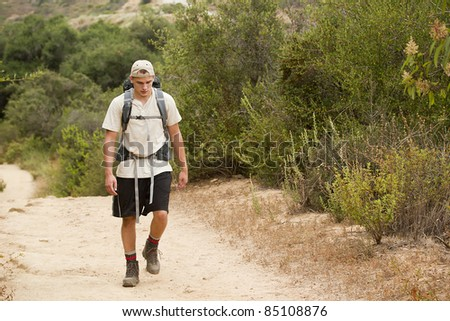 A young male walking on a mountain trail during a hiking trip. - stock photo
