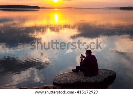 a young man,alone, sitting on a rock on the shore of the lake admiring the beautiful sunset and sky. In the hands holding the phone - stock photo