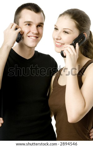 A young man and a young woman both using mobile phones - stock photo