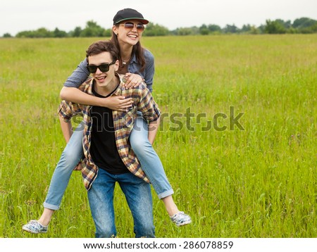 A young man and a young woman having fun outdoors - stock photo