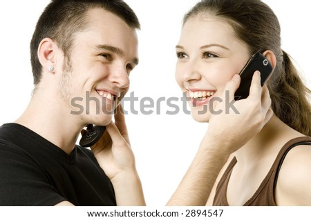 A young man and a young woman swapping phones on white background - stock photo