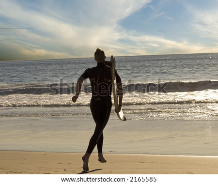 a young man and his surfboard are running into the ocean to go surfing - stock photo