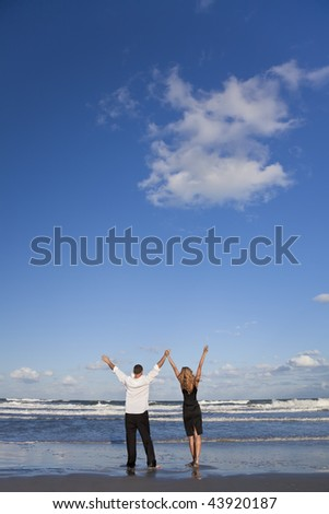 A young man and woman celebrating arms raised and holding hands as a romantic couple on a beach with a bright blue sky