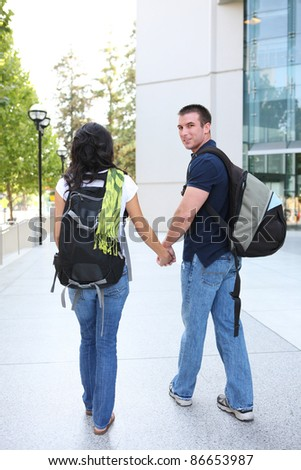 A young man and woman couple in love at the school library - stock photo
