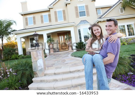 A young man and woman couple in love in front of their new home - stock photo