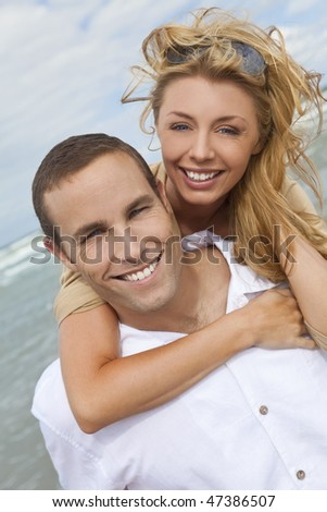 A young man and woman embracing as a romantic couple laughing and having fun on a beach