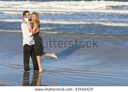 A young man and woman embracing as a romantic couple on a beach - stock photo