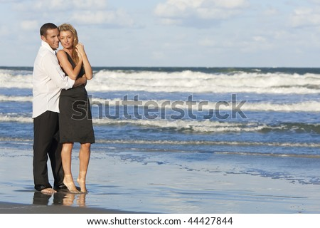 A young man and woman embracing as a romantic couple standing in the sea on a beach with a blue sky - stock photo