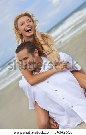 A young man and woman having fun as a romantic couple on a beach with the man carrying the woman on his back piggy back style. - stock photo