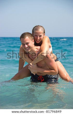 A young man and woman having fun as a romantic couple on a beach with the man carrying the woman on his back piggy back style