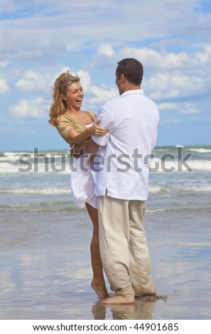 A young man and woman having fun laughing and embracing as a romantic couple on a beach with a bright blue sky - stock photo