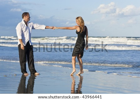 A young man and woman holding hands and having fun dancing as a romantic couple on a beach with a bright blue sky and sea - stock photo