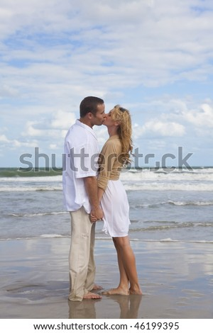 A young man and woman holding hands and kissing as a romantic couple on a beach - stock photo