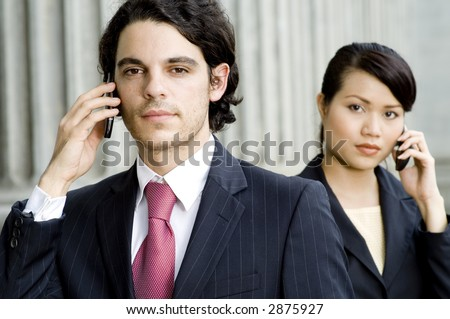 A young man and woman in business attire holding mobile phones outdoors
