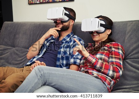 A young man and woman in casual clothes and virtual reality glasses are very excited - stock photo