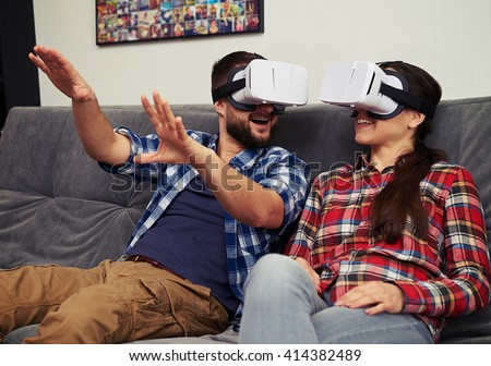 A young man and woman in casual clothes having fun using white virtual reality glasses - stock photo