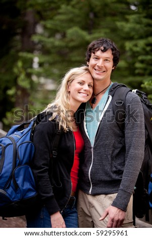 A young man and woman outdoors in the forest - stock photo