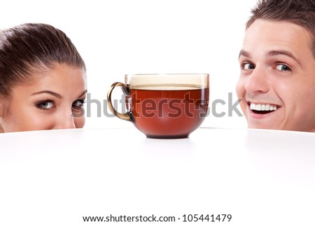 A young man and woman peeking from under the table at a large cup of tea