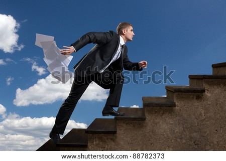 A young man aspiring up the ladder with the emitted sheets of paper