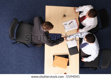A young man at a a job interview with two interviewers, handshake.Aerial shot taken from directly above the table. - stock photo