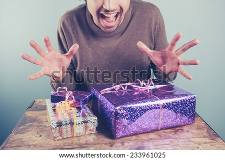 A young man at a table is excited about opening  his presents - stock photo