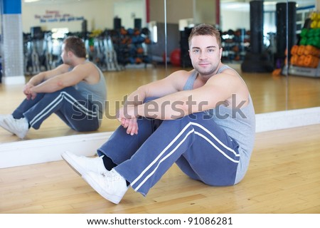 A young man at the gym sitting next to a large mirror - stock photo