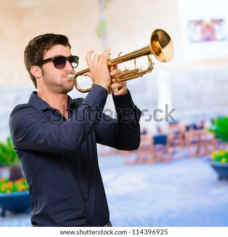 A Young Man Blowing A Trumpet, Outdoor