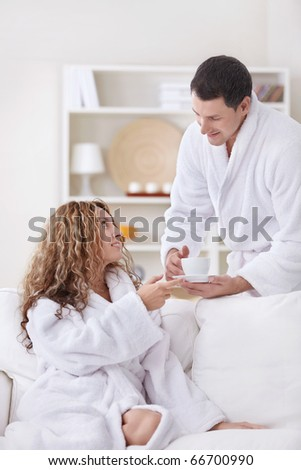 A young man brings coffee beautiful girl - stock photo
