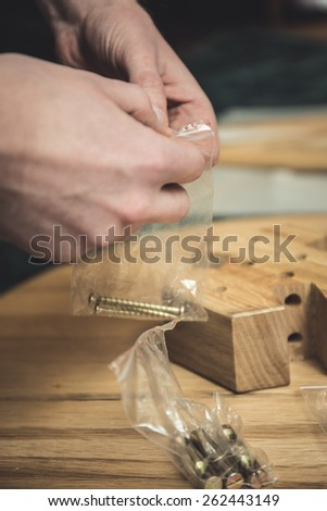 A young man builds a table together