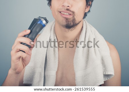 A young man cannot finish shaving because his electric razor is broken - stock photo