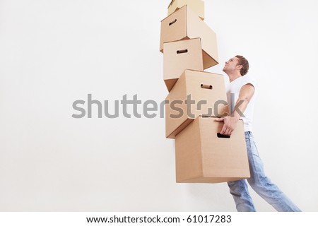 A young man carries a large number of boxes - stock photo