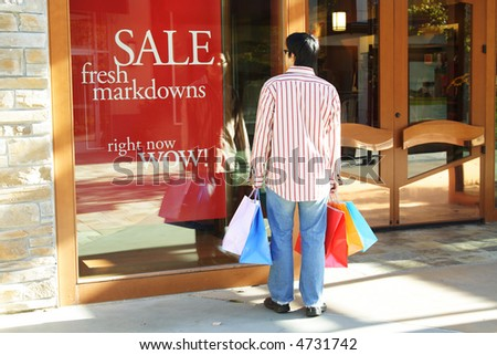 A young man carrying shopping bags looking at sale sign at an outdoor shopping mall
