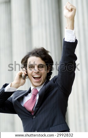 A young man celebrating business success outside