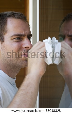 A young man cleaning the window on his house with a paper towel. - stock photo