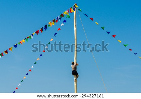 A young man climbs a pole for fun during the holiday Sabantuy