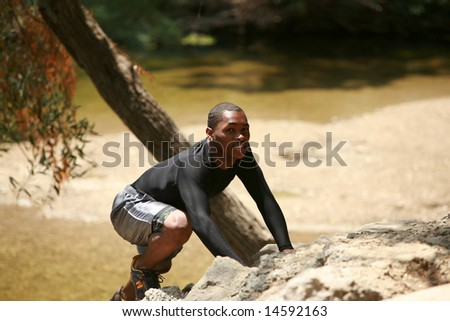 a young man climbs a rock outside - stock photo