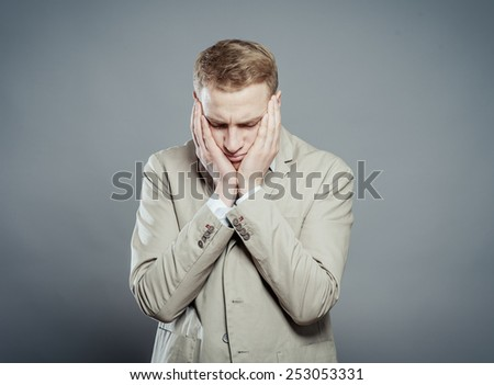 A young man close-up in a suit on a gray background, fall asleep, tired man,stressed and with headachetired man,stressed and with headache. The guy wants to sleep. Gesture. Photos - stock photo