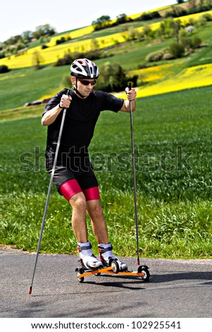 A young man cross-country skiing with roller ski - stock photo