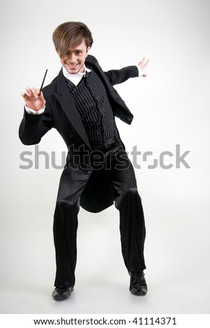 A young man dancing in a black tailcoat is pointing the stick to the camera and smiling - stock photo