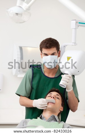 A young man dentist preparing an x-ray - stock photo