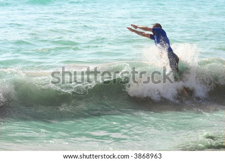 A young man diving into the waves