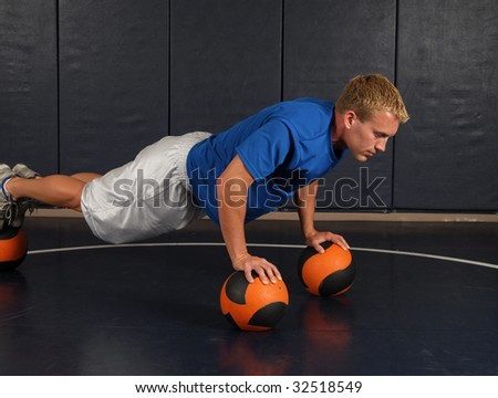 A young man doing push ups in the gym - stock photo