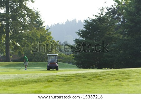 A young man, dressed in a green polo, prepares to drive a golf shot down range. Horizontally framed shot. - stock photo