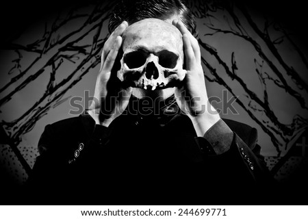 A young man dressed in black with a skull in his hands. Black and white.  - stock photo