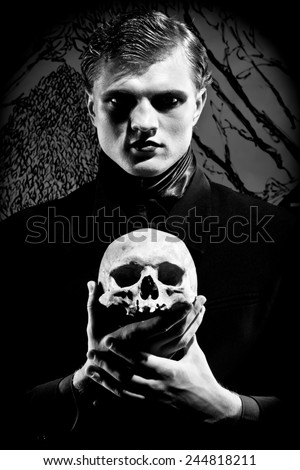 A young man dressed in black with a skull in his hands. Black and white. Artistic background created by me - stock photo