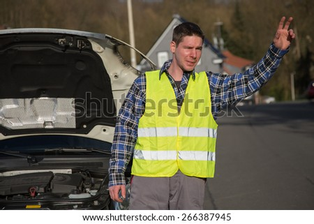 A young man dressed with a reflective vest asks for help on the road near his broken car. - stock photo