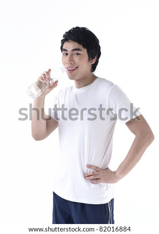 A young man drinking water after exercise - stock photo