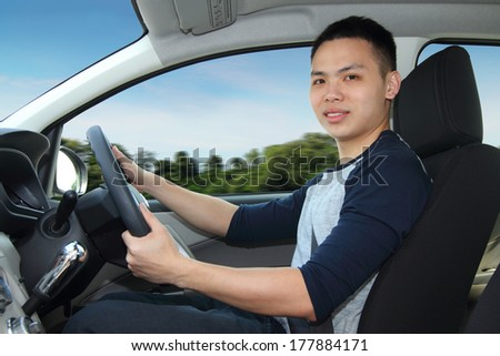 A young man driving a car - stock photo