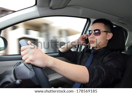 A young man driving while talking on a mobile phone - stock photo