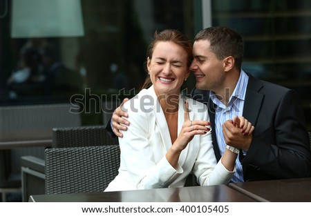 A young man embraces a woman sitting in a cafe , they laugh - stock photo